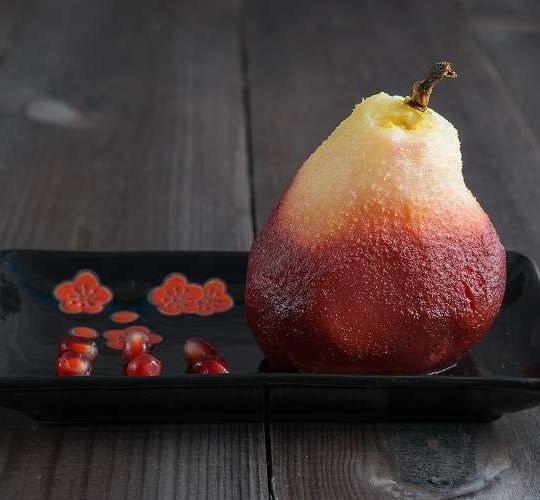 one poached pear on black rectangle plate with red pomegranate seeds on dark wooden background